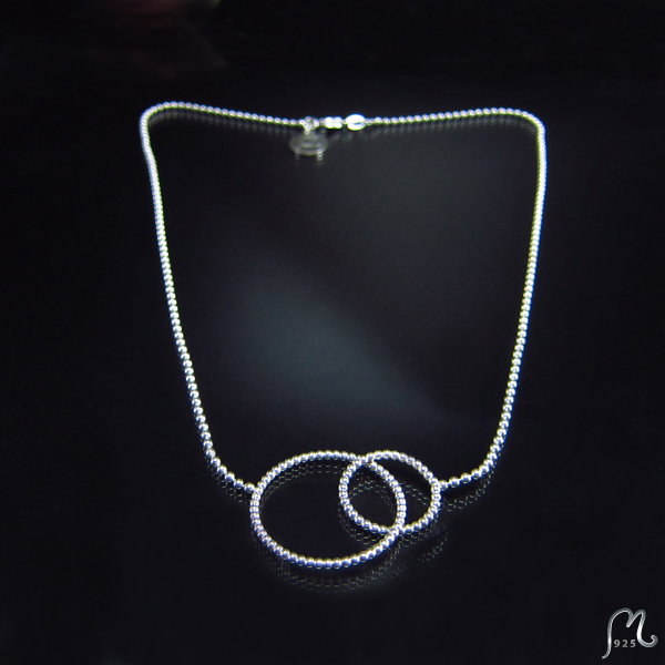 Silver necklace with two rings.
